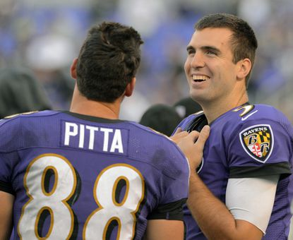 Ravens quarterback Joe Flacco stands on the sidelines with tight end Dennis Pitta against the Raiders in November.