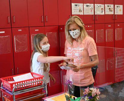 Fourth-grade teacher Tina Purtell talks with student Chloe Watts as she looks over the gift card inside the thank you card as Watts arrives for the last day of school at Emmorton Elementary School Monday, June 14, 2021.