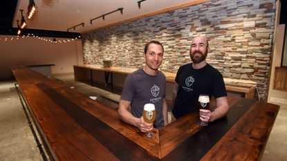 Sapwood Cellars owners Scott Janish, left, and Michael Tonsmeire hold up beers in their under-construction brewery/taproom. They expect to open in June.