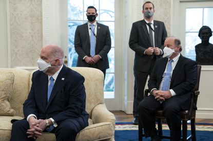 Maryland Gov. Larry Hogan, left, and Detroit Mayor Mike Duggan listen as President Joe Biden speaks during a meeting with a bipartisan group of mayors and governors to discuss a coronavirus relief package in the Oval Office.
