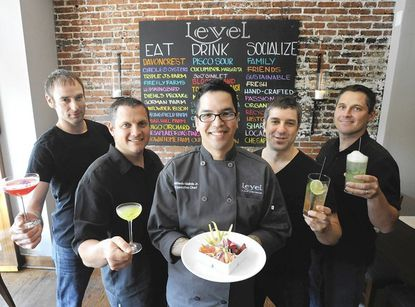 Level's Executive Chef Alfredo Malinis Jr. holds house-pickled local vegetables for $7. With him from left are co-owners, John Miller; Chris Fox; John Hogan; and Andrew Fox.