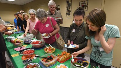 Twin sisters Marcie, second from right, and Tess McRae help themselves to dessert at the Forks Over Knives Meetup Potluck dinner at the Triadelphia Seventh-day Adventist Church in Clarksville.