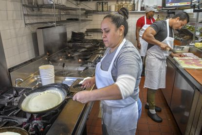 Maria Mejia prepares crepes in the kitchen at Pasta Plus in Laurel. She's celebrating her 25th year at the restaurant.