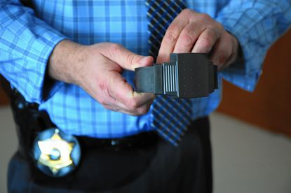 Gregory Shields, director of Cook County Sheriff's electronic home monitoring program, shows an electronic ankle bracelet.