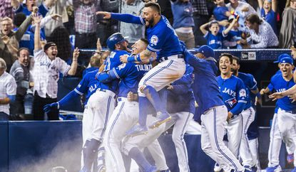 Toronto Blue Jays players celebrate their walk-off win in Game 3 to eliminate the Texas Rangers in the American League division series on Sunday.