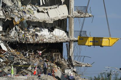 A crane is used to remove sets of human remains, as search and rescue personnel work atop the rubble at the Champlain Towers South condo building, where scores of people remain missing more than a week after it partially collapsed, Friday, July 2, 2021, in Surfside, Florida. (AP Photo/Mark Humphrey)