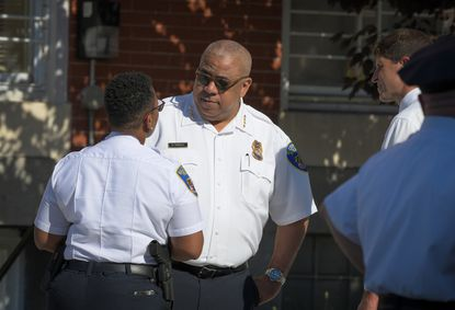 Baltimore Police Commissioner Michael Harrison talks with police department personnel at the scene of a shooting at the Man Alive drug treatment center on Maryland Avenue in July.