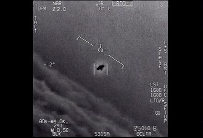 """The image from video provided by the U.S. Department of Defense labelled Gimbal, from 2015, an unexplained object is seen at center as it is tracked as it soars high along the clouds, traveling against the wind. """"There's a whole fleet of them,"""" one naval aviator tells another, though only one indistinct object is shown. """"It's rotating."""" The U.S. government has been taking a hard look at unidentified flying objects, under orders from Congress, and a report summarizing what officials know is expected to come out in June 2021. (Department of Defense via AP)"""