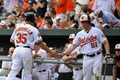 Lew Ford (right) gives a low five to Orioles teammate Omar Quintanilla during Sunday's game against the A's -- Ford's first in the majors since the end of the 2007 season.