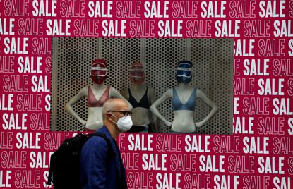 A man wearing a protective face mask walks past a shop window in London on July 14, 2020. Britain's government is now demanding people wear face coverings in shops as it has sought to clarify its message after weeks of prevarication amid the COVID-19 pandemic.