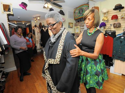 Barbara Griffin, of Arbutus, tries on an item at 2 Chic Boutique, with help from State Sen. Catherine Pugh, one of the owners of the Pigtown consignment shop.