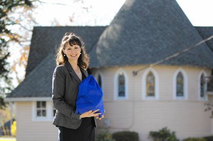 Monica Butta stands outside Church of the Holy Comforter in Lutherville, holding a backpack filled with enough food for a weekend. The church assembles and delivers the backpacks to an area school for homeless children for the weekend.