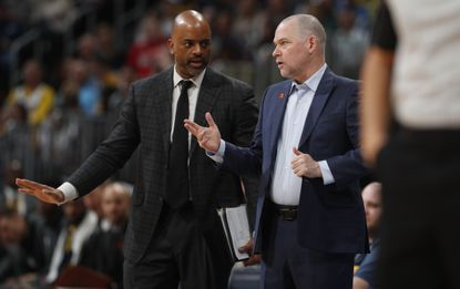 Denver Nuggets assistant coach Wes Unseld Jr., left, confers with head coach Michael Malone during a game Jan. 26, 2020, in Denver.