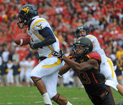 West Virginia's Tavon Austin (formerly of Dunbar) fumbles the ball out of bounds as he's tackled by Maryland's Kerry Boykins during a kick return in the first quarter.
