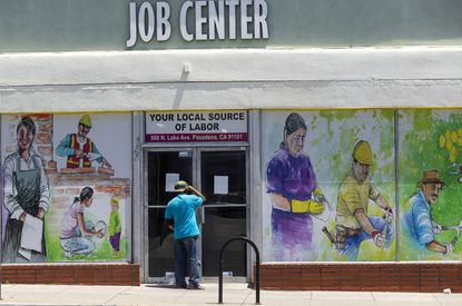 A person looks inside the closed doors of the Pasadena Community Job Center May 7, 2020, in Pasadena, California. Nearly 1.2 million laid-off Americans applied for state unemployment benefits last week, the 20th straight week that at least 1 million people have sought jobless aid.