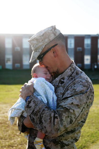 Sgt. Judah Kelber, just off the bus at Camp Lejeune, N.C., snuggles his son Aaron, just shy of 10 weeks old, for the first time after returning from a seven-month deployment to Afghanistan March 6.