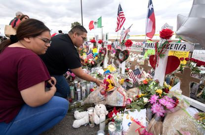 People place flowers at a makeshift memorial for shooting victims at the Cielo Vista Mall Walmart, in El Paso, Texas, on August 6, 2019. The August 3 shooting left 22 people dead. President Donald Trump will visit the Texan border city August 7, and will also travel to Dayton, Ohio where a second mass shooting early August 4 left another nine dead.