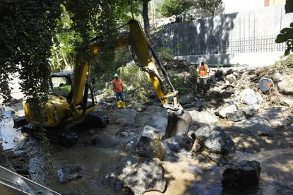 A worker with Potts & Callahan uses an excavator to move large rocks and pieces of retaining walls that were sent down the Hudson Branch during historic flooding on July 30. The U.S. Army Corps of Engineers, Baltimore District, clears the Hudson River, one of two waterways blocked by storm debris.
