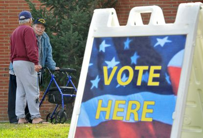 School and election officials in the city of Baltimore and Baltimore and Howard counties are grappling with the need to hold a special primary Feb. 4. In this 2014 file photo, voters talk outside a school polling place.