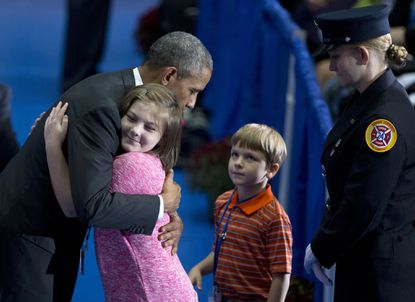 President Barack Obama hugs a young girl as he greets family members and coworkers of fallen firefighters during the National Fallen Firefighters Memorial Service at Mount St. Mary's University in Emmitsburg.