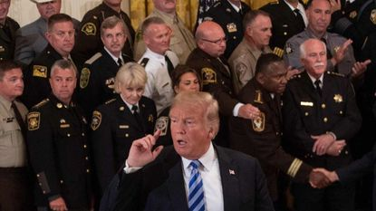 President Trump listens to a journalist's question during a meeting with sheriffs at the White House.