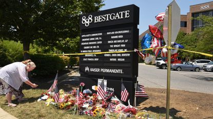 Erin Monfort of Brandywine, takes a photo outside 888 Bestgate Road, where five Capital Gazette staffers were killed in a shooting in their office.