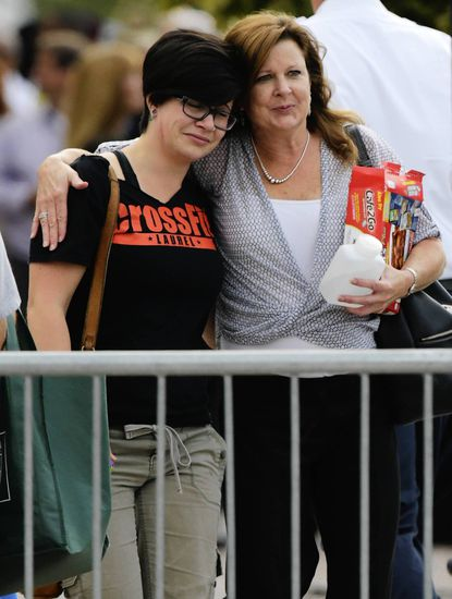Kayla Yi, left, and her mother, Donna Richardson embrace near the Navy Yard in Washington in the aftermath of the shooting Monday. Richardson, a Bel Air resident, works in the building where 12 people were killed.