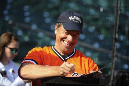 Reality star Mike Rowe, who is not a suspect in an Oregon bank robbery, signs autographs before a 2014 Orioles game. Note the baseball cap...