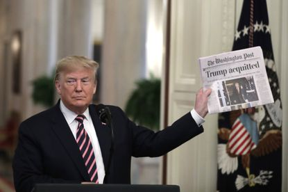 President Donald Trump holds a newspaper in the East Room at the White House in Washington as he delivers remarks about his Senate impeachment trial on February 6, 2020.