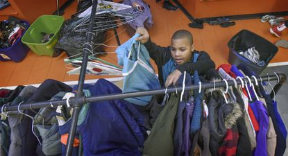 Darrick Adams, an Oakland Mills Middle School sixth grader, is among those sorting clothes Monday afternoon in preparation for a distribution event. The Columbia Association's Youth and Teen Center and its Teen Outreach Committee will be distributing free clothing to those in need on January 16 and 17 at the Barn in the Oakland Mills Village Center.