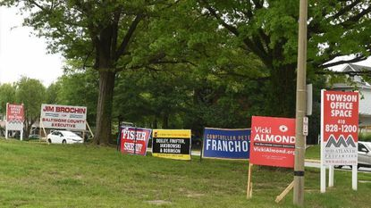 Dueling election signs are seen on a vacant lot at the intersection of Bosley Avenue and Joppa Road in Towson on June 7.