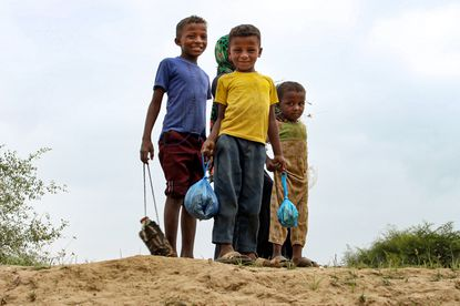 Children look on as they hold plastic bags and water bottles at a make-shift camp for displaced Yemenis in the northern Hajjah province on December 16, 2019. (Essa Ahmed/AFP)