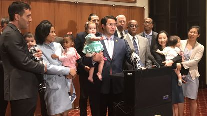 "A majority of the Baltimore City Council is supporting Isaac ""Yitzy"" Schleifer's bill to require baby changing stations be installed in more establishments. Schleifer addresses reporters Monday outside council chambers with his 15-month-old daughter, Bobbi Bella."
