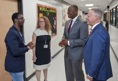 Howard County Superintendent Michael Martirano (R) and Howard County Executive Calvin Ball chat with paraeducator, Gregory Campbell and principal, Melissa Shindel on the first day of school at Lake Elkhorn Middle School Tuesday morning in Columbia.