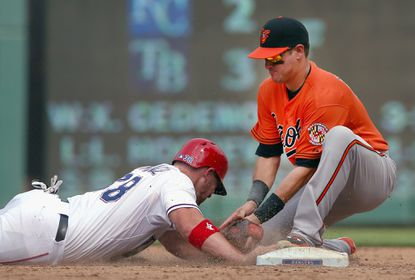 Paul Janish #15 of the Baltimore Orioles tags out Chris Gimenez #38 of the Texas Rangers for the out at secodn base in the bottom of the sixth inning at Globe Life Park in Arlington on August 30, 2015 in Arlington, Texas.