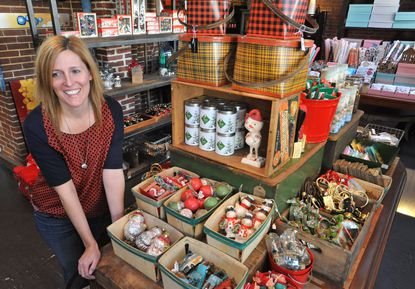 Carmen Brock, the owner of Trohv in Hampden, pauses near a new display of Christmas ornaments.