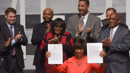 Baltimore Mayor Catherine Pugh holds the cover letter of the city's proposal to locate Amazon's second headquarters (HQ2) in Baltimore after a signing ceremony at City Garage last month.