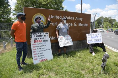 "The protesters, from left, Willis Moore, U.S. Army veteran, Lewis A. Bracy, U.S. Army veteran, Vic Hayes, U.S. Air Force veteran, and Charles James Sr., U.S. Army veteran, in front of Ft. Meade's main gate. Lewis A. Bracy, a retired NSA Security Officer and Military Veteran, organized a small protest against President Donald Trump's ""hiding the ""Bounty Gate"" facts"", at the National Security Agency and at Fort Meade Thursday."
