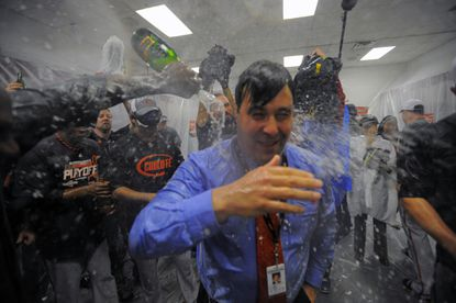 Orioles executive vice president Dan Duquette gets doused in champagne in the clubhouse after the wild-card win.