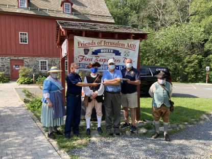 The Friends of Jerusalem Mill had to cancel its fifth annual First Responder's Day due to the coronavirus pandemic, but presented $500 donations to both the Joppa Magnolia and Kingsville volunteer fire companies. Pictured, from left to right, are Diane Pry, history interpreter; Bob Chaney, President, Kingsville Volunteer Fire Company; Harry Sanders, Founder of Friends of Jerusalem Mill; Rick Decker, President, Friends of Jerusalem Mill Board of Directors; William Vanarsdale, Jr., Chief, Joppa-Magnolia Volunteer Fire Company; and Hugh Pry, history interpreter.