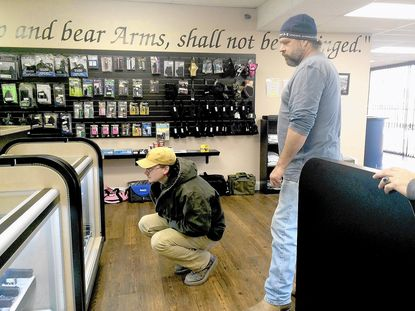 A customer browses the inventory at Worth-A-Shot Firearms in Millersville on Tuesday. The store displays the Second Amendment to the U.S. Constitution on its walls.