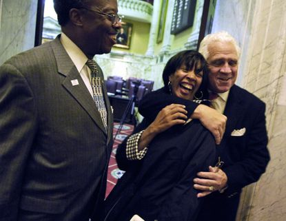 """In happier times outside the Senate Chamber, then-Sen. Catherine Pugh receives a hug from Senate President Thomas V. Mike Miller as she and then-Sen. Nathaniel J. McFadden prepared to leave the building. Senator Pugh pleaded guilty last month to federal charges of wire fraud, conspiracy and tax evasion in connection to her """"Healthy Holly"""" book scheme."""