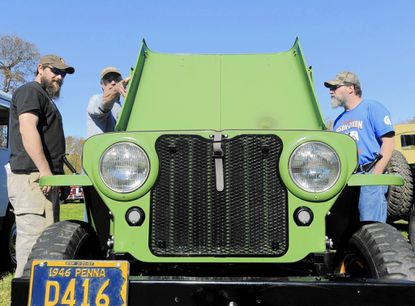 Chad Hutzell, Ed Smiley and Art Mulkey get a look at a 1946 CJ2A belonging to Adam and Frank Buck of Gettysburg, Pa. during the 8th annual Mason-Dixon Willys Jeep Gathering at Union Mills Homestead Sunday, Oct. 26, 2014.