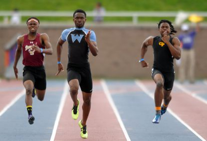 Western Tech's Carrington Akosa, center, won three individual state title at the Class 2A boys outdoor track and field state championships.