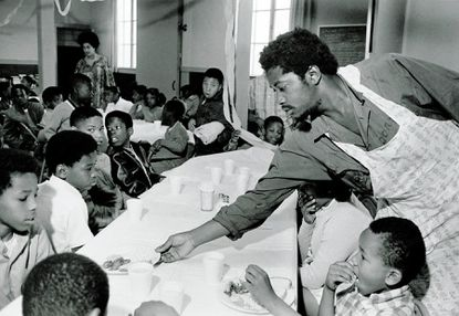 Black Panther Party member Charles Bursey serves a table of kids during one of the group's free breakfasts for schoolchildren.