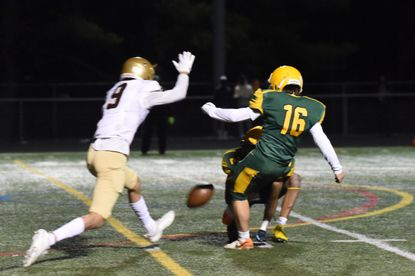 Wilde Lake kicker Grant Gladden (16) squeaks his third field goal of the game past a block attempt by Hammond's Micah Austin, to win a 9-6 a football game at Wilde Lake High School on Friday, March 12, 2021.