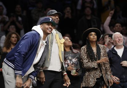 Carmelo Anthony, left, LeBron James, second from left, and Gabrielle Union, second from right, watch as Miami Heat guard Dwyane Wade plays his final NBA basketball game, against the Brooklyn Nets on Wednesday, April 10, 2019, in New York. (AP Photo/Kathy Willens)