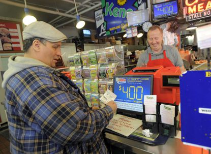 Larry Jacobs of South Baltimore buys a Mega Millions ticket from Henry Reisinger, the owner of the Fenwick Meats stand in Cross Street Market.