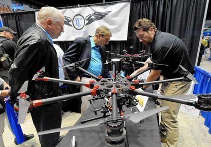 Staff from Total Control Innovations demonstrate a drone during the commercial drone industry's first expo in L.A. this month.