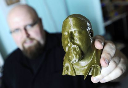Russ Reese of Glen Burnie holds a plastic bust of himself that he created at a three-dimensional scanning and printing station at Atomic Books in Hampden.